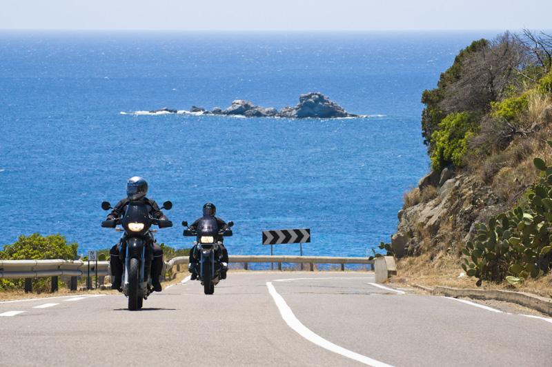 Motociclisti ammirano il panorama della costa in Sardegna