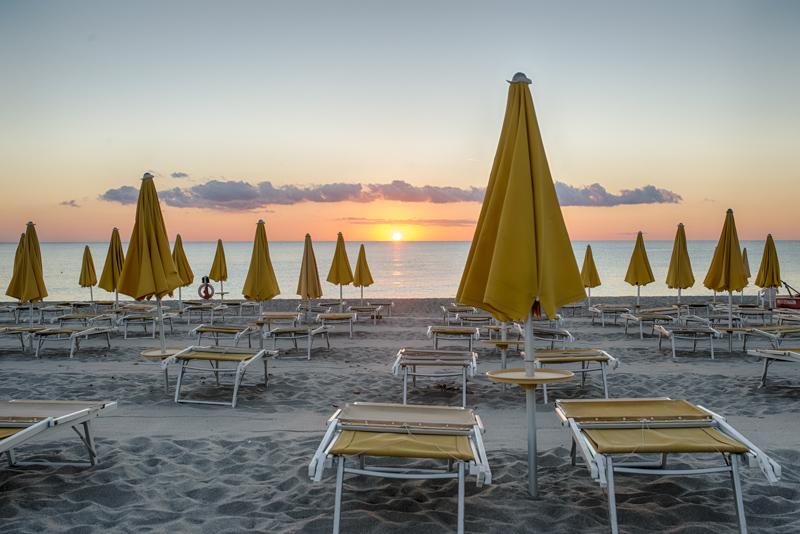 La spiaggia all'alba con gli ombrelloni chiusi